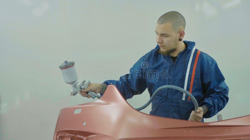 Auto målare som besprutar röd målarfärg på den främre stötdämparen för bil i specialt bås royaltyfri foto