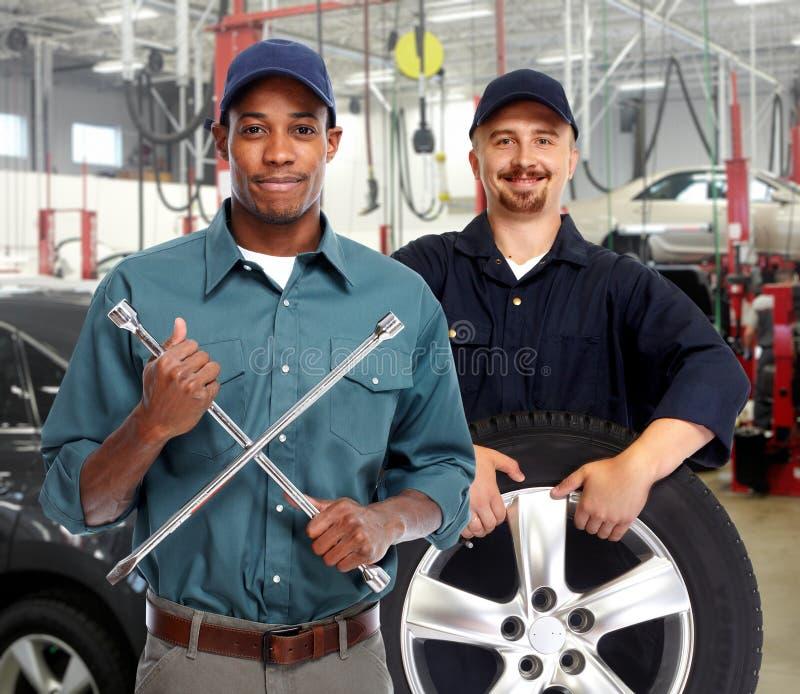 Auto mecânico com a chave do pneu na garagem imagens de stock royalty free