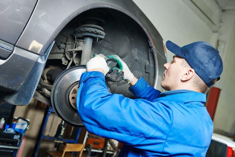 Auto mecânico na reparação dos freios do carro imagens de stock royalty free