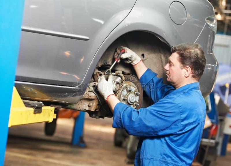 Auto mecânico no trabalho do reparo da suspensão do carro foto de stock royalty free