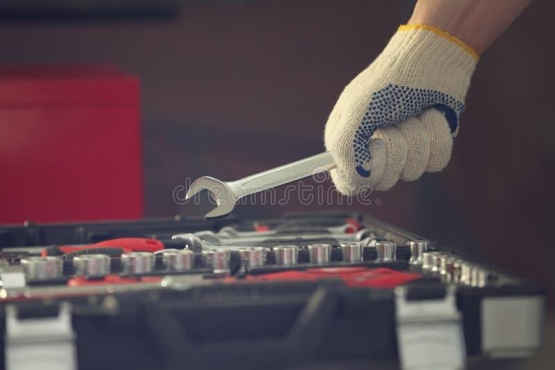 Auto mecânico que seleciona ferramentas na oficina de reparações do carro imagem de stock