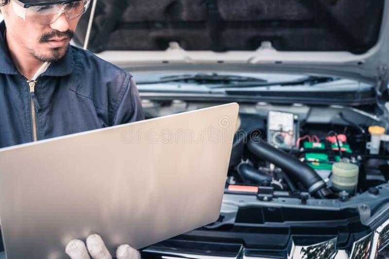 Auto mecânico que trabalha em um computador conectado a um motor de automóveis na oficina de reparações foto de stock