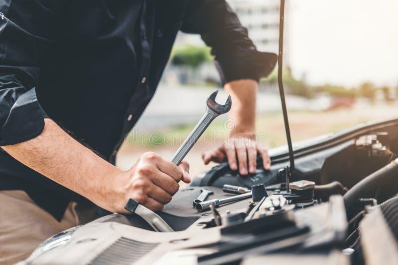 Auto mecânico que trabalha no técnico Hands da garagem do mecânico de carro que trabalha verificação no carro do serviço e da man foto de stock