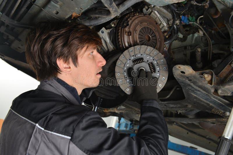 Auto mecânico que trabalha sob o carro e a embreagem em mudança imagens de stock royalty free