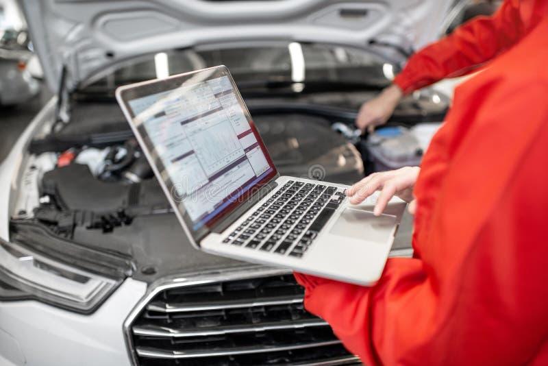 Auto mecânicos que fazem diagnósticos com portátil imagem de stock