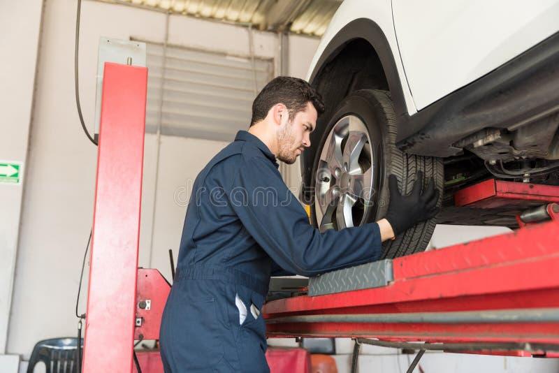 Auto Mechanic Adjusting Car Tire In Repair Shop. Side view of auto mechanic adjusting car tire in repair shop stock photography