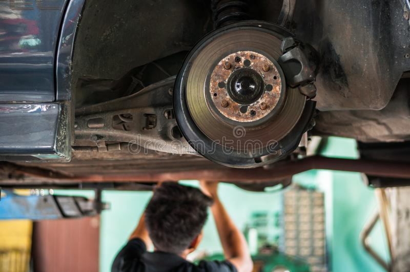 Auto mechanic asian checking bush-bolt under double wishbone suspension by hand with tools car lift. Auto mechanic asian, checking bush-bolt, under double royalty free stock photos