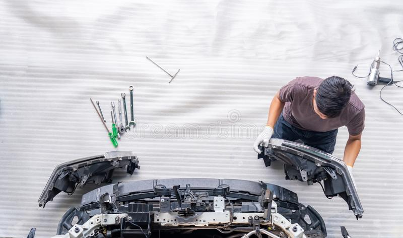 Auto mechanic is assembling car parts. Mechanic changing car headlight in a workshop ,white background ,Top view royalty free stock photo