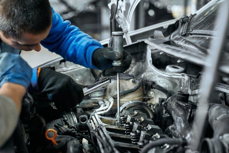 Auto mechanic in blue uniform replacing glow plugs in engine stock photo