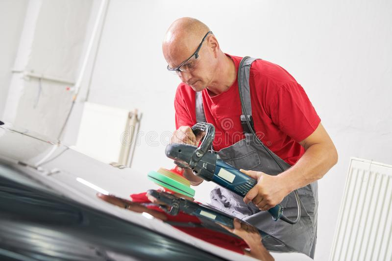 Auto mechanic buffing car autobody. Auto body repairs. Mechanic worker burnish and polishing automobile car body by buffing grinding machine in garage workshop royalty free stock photo