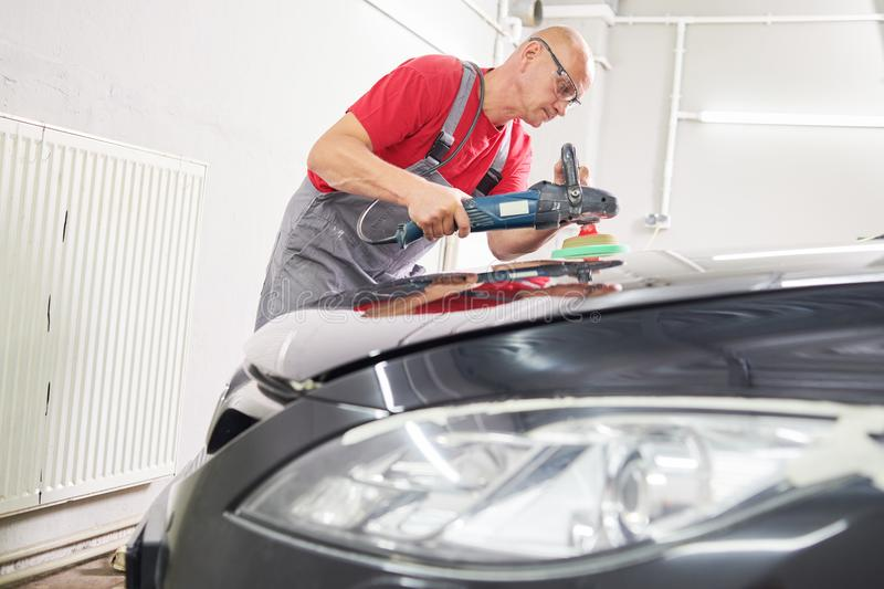 Auto mechanic buffing car autobody. Auto body repairs. Mechanic worker burnish and polishing automobile car body by buffing grinding machine in garage workshop stock image