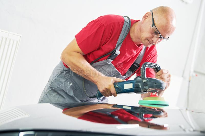 Auto mechanic buffing car autobody. Auto body repairs. Mechanic worker burnish and polishing automobile car body by buffing grinding machine in garage workshop royalty free stock photos