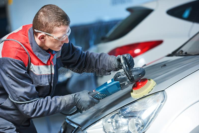 Auto mechanic buffing car autobody. Auto body repairs. Mechanic worker burnish and polishing automobile car body by buffing grinding machine in garage workshop royalty free stock photography