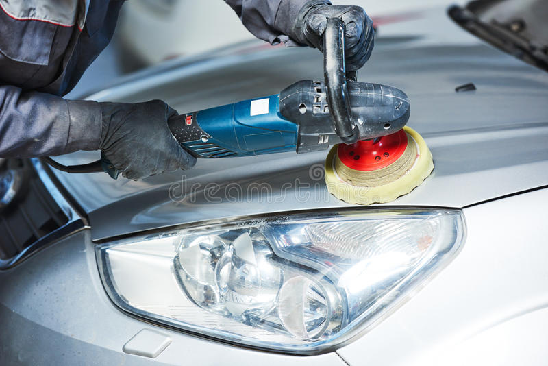 Auto mechanic buffing car autobody bonnet. Auto body repairs. Mechanic worker burnish and polishing automobile car bonnet by buffing grinding machine in garage stock image