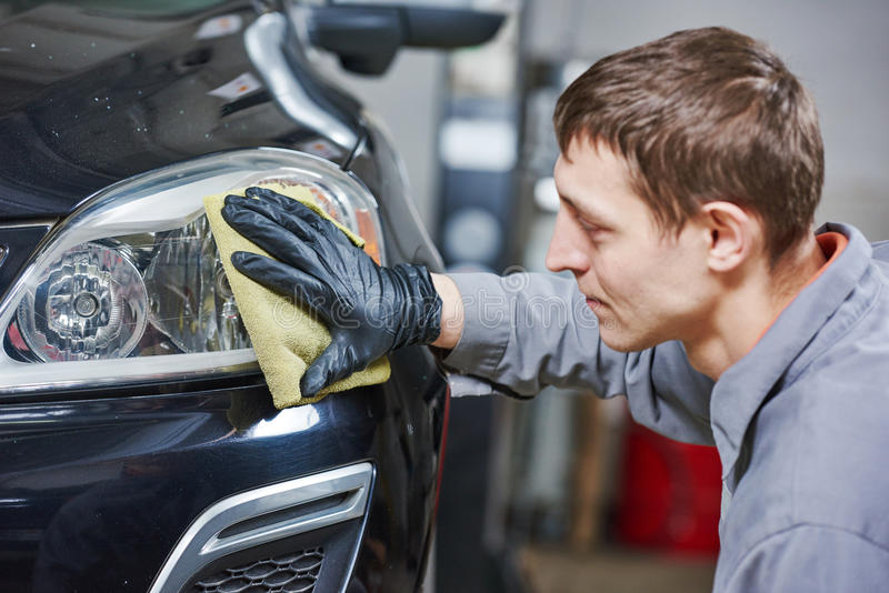 Auto mechanic buffing and polishing car headlight. Auto body repairs. Mechanic worker burnish and polishing automobile car headlight in garage workshop stock photo