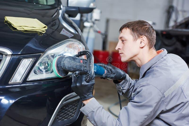 Auto mechanic buffing and polishing car headlight. Auto body repairs. Mechanic worker burnish and polishing automobile car headlight by buffing grinding machine stock photography