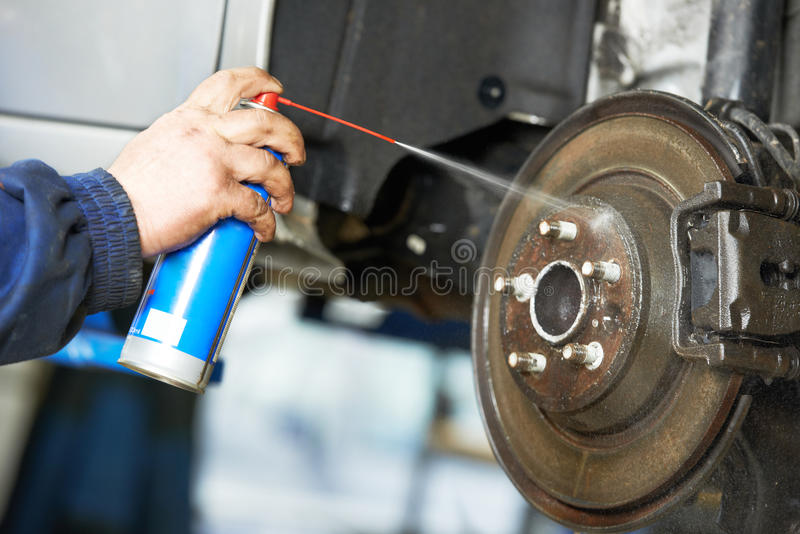 Auto mechanic at car suspension repair work stock images