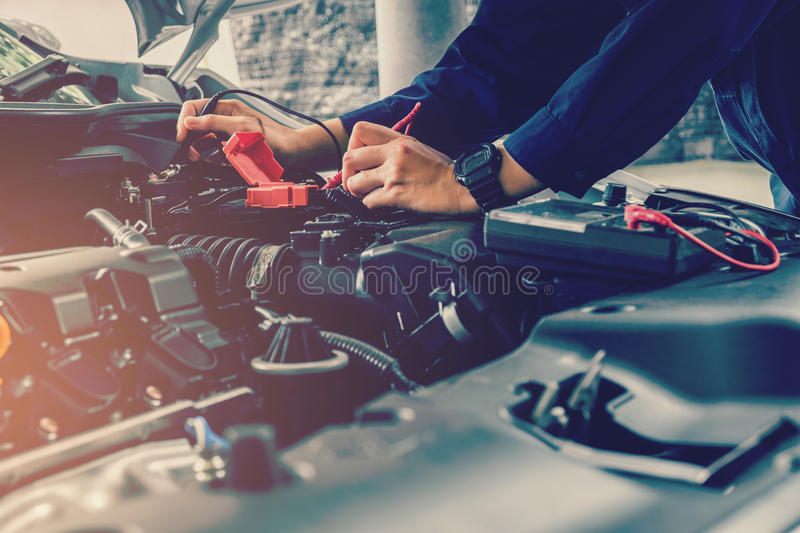 Auto mechanic checking car battery voltage royalty free stock photography