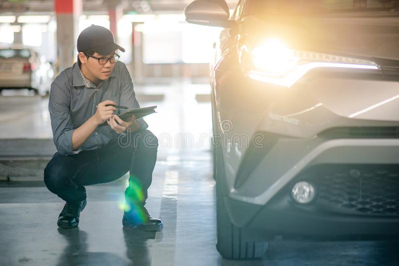 Auto mechanic checking car headlight using tablet. Young Asian auto mechanic holding digital tablet checking headlight in auto service garage. Mechanical royalty free stock image