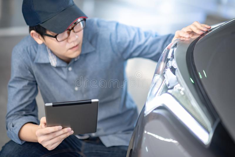 Auto mechanic checking car headlight using tablet. Young Asian auto mechanic holding digital tablet checking headlight in auto service garage. Mechanical stock photography