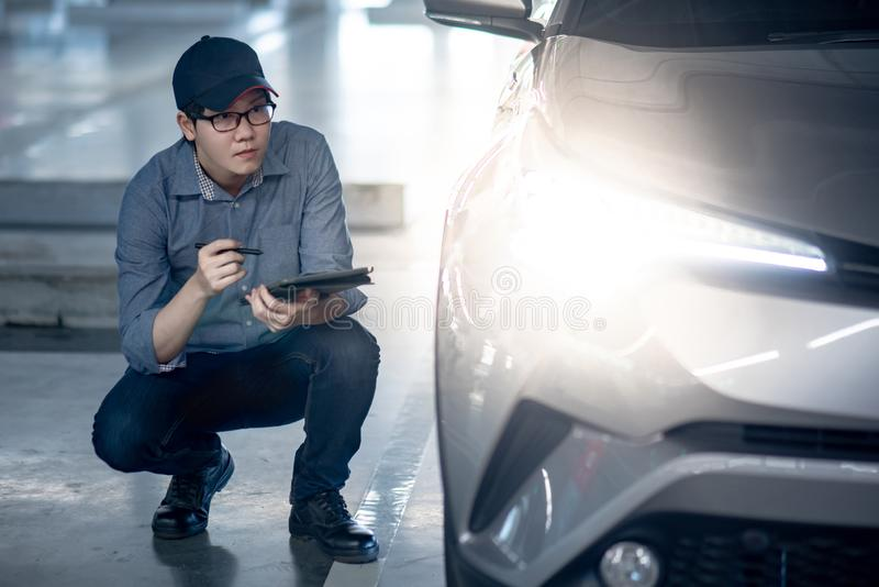 Auto mechanic checking car headlight using tablet. Young Asian auto mechanic holding digital tablet checking headlight in auto service garage. Mechanical royalty free stock photo