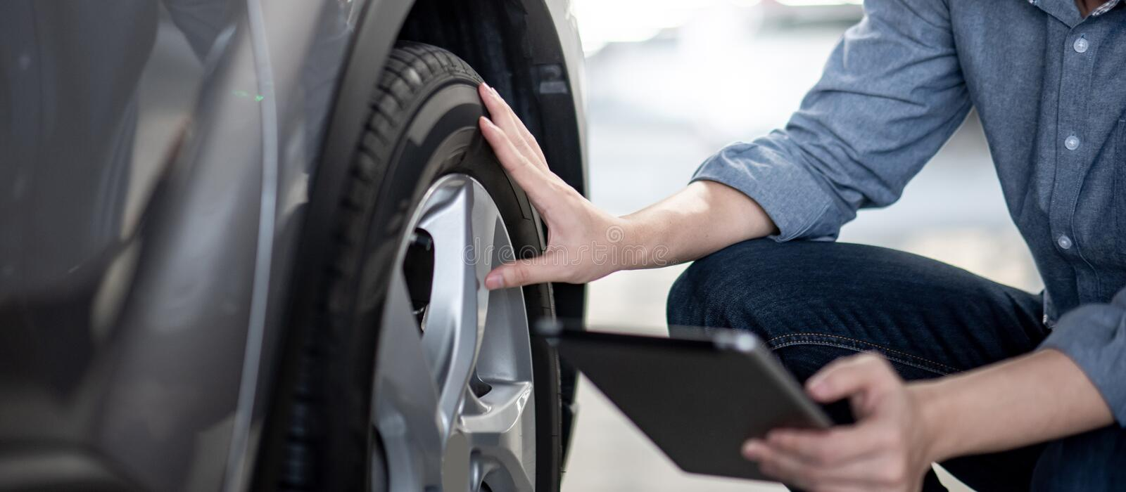 Auto mechanic checking the car using tablet. Asian auto mechanic holding digital tablet checking car wheel in auto service garage. Mechanical maintenance royalty free stock images