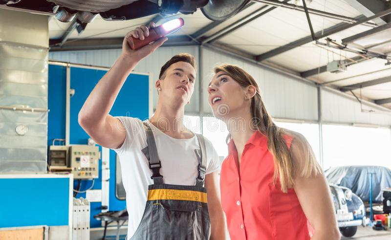 Auto mechanic checking the disk brake rotors of the car of a fem royalty free stock image