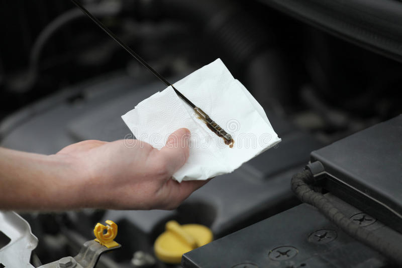 Auto mechanic checking engine oil dipstick in car stock photos
