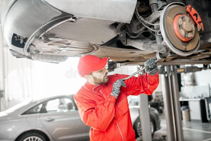 Auto mechanic diagnosing car at the car service. Auto mechanic in red uniform diagnosing car on the hoist at the car service royalty free stock photo