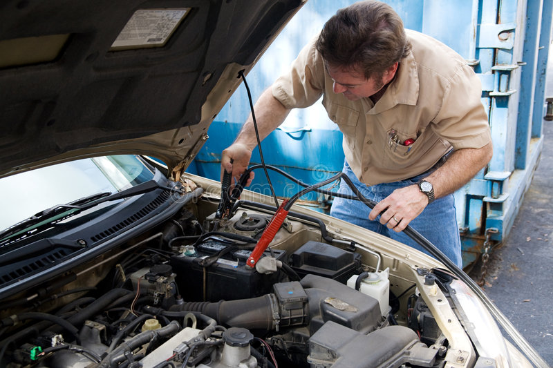 Auto Mechanic - Jumper Cables. Auto mechanic using jumper cables to charge a car battery royalty free stock images