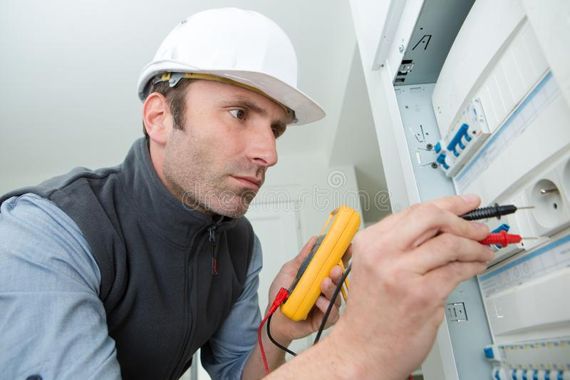 Auto mechanic man with multimeter testing fuseboard stock images