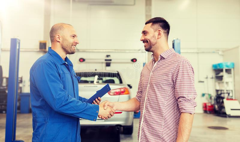 Auto mechanic and man shaking hands at car shop. Auto service, repair, maintenance, gesture and people concept - mechanic with clipboard and men or owner shaking royalty free stock photography