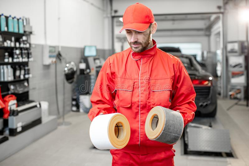 Auto mechanic with new and used car air filter. Auto mechanic in red uniform holding new and used air filter standing at the car service royalty free stock image
