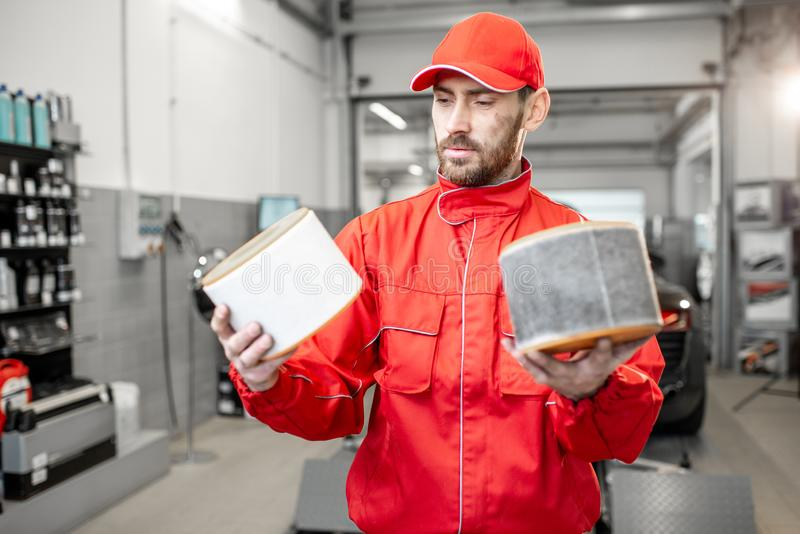 Auto mechanic with new and used car air filter. Auto mechanic in red uniform holding new and used air filter standing at the car service stock photography