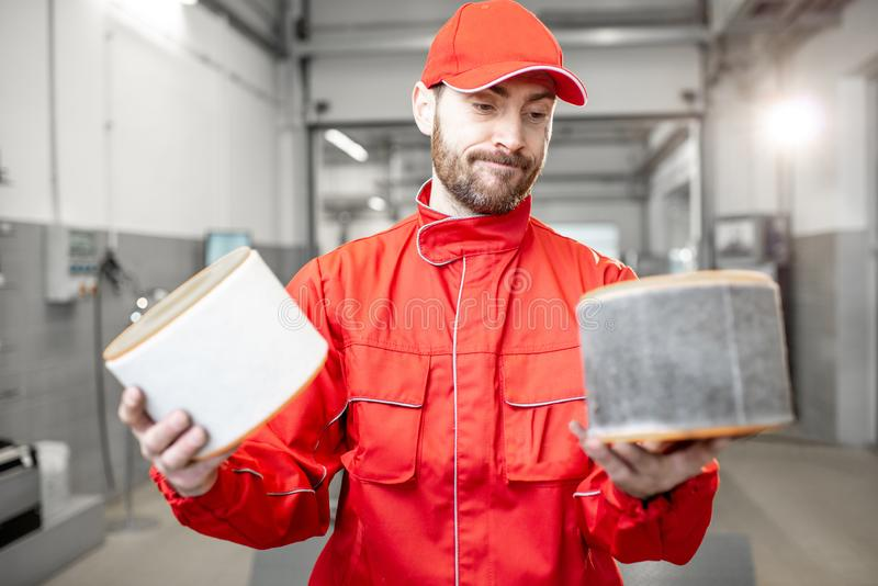 Auto mechanic with new and used car air filter. Auto mechanic in red uniform holding new and used air filter standing at the car service royalty free stock photos