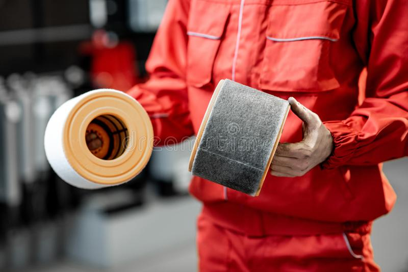 Auto mechanic with new and used car air filter. Auto mechanic in red uniform holding new and used air filter standing at the car service, close-up view with no royalty free stock images