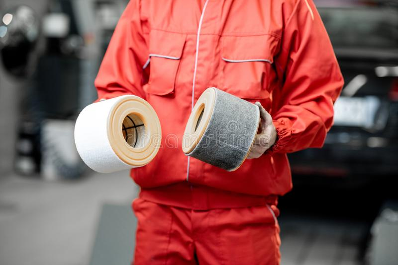 Auto mechanic with new and used car air filter. Auto mechanic in red uniform holding new and used air filter standing at the car service, close-up view with no stock image