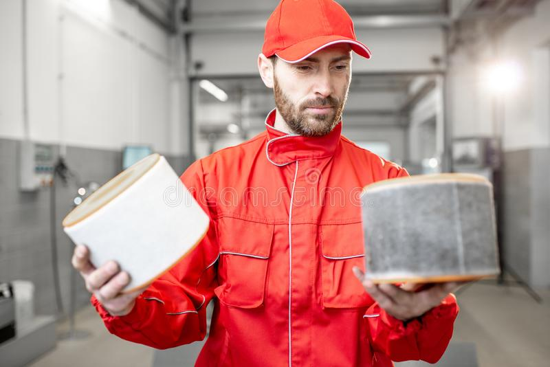 Auto mechanic with new and used car air filter. Auto mechanic in red uniform holding new and used air filter standing at the car service stock photo