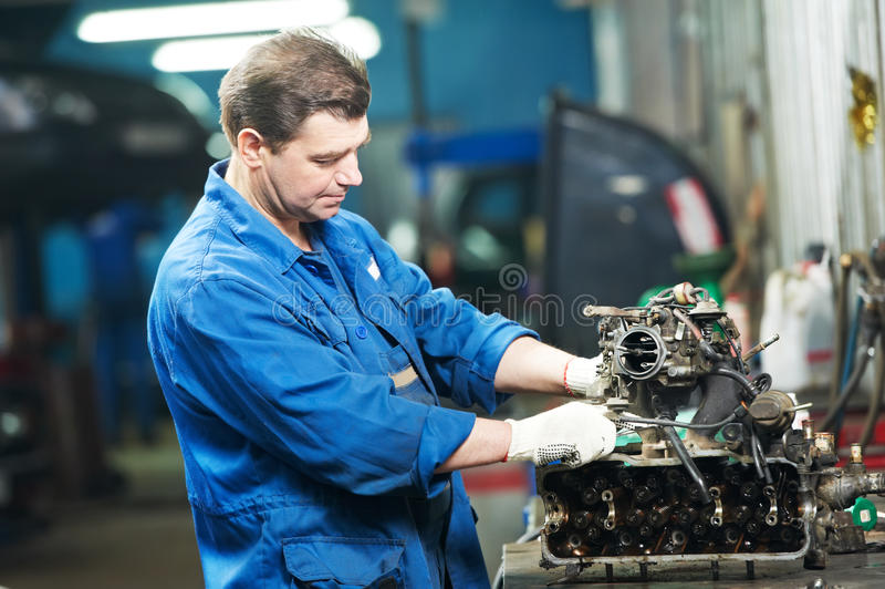 Auto mechanic at repair work with engine stock photography