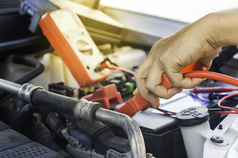 Auto mechanic uses a charging battery with electricity trough jumper cables in a car. stock images