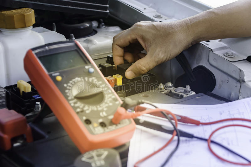 Auto mechanic uses a multimeter voltmeter. stock image