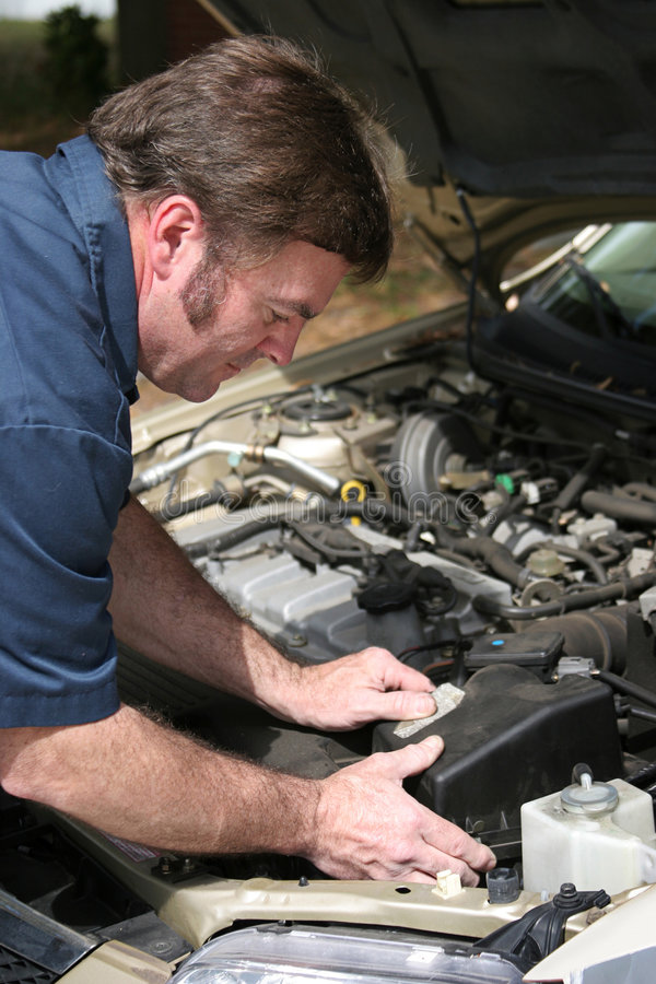 Auto Mechanic Working. An auto mechanic working on a car royalty free stock photo