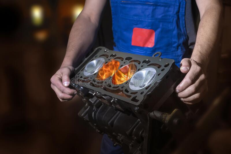 Auto mechanic working in a garage. Burning fire flame on engine piston. Repair service royalty free stock photos