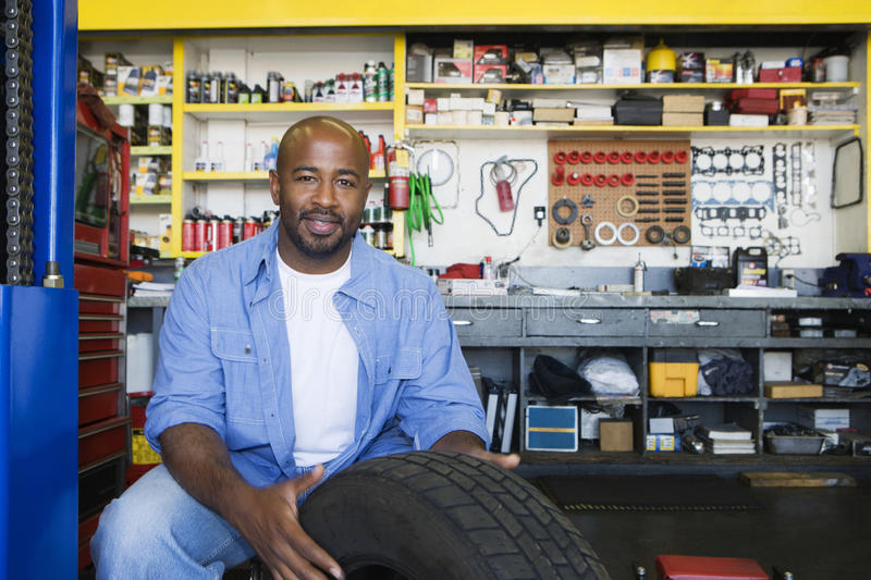 Auto Mechanic Working On A Tire. Portrait of a happy African American male mechanic working on a tire stock images