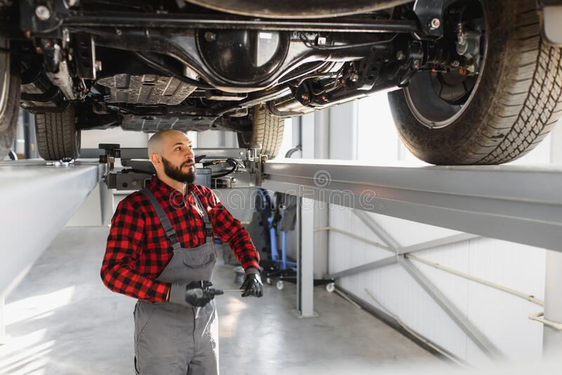 Auto mechanic working underneath a lifted car. Auto mechanic working in garage. Repair service.  royalty free stock image