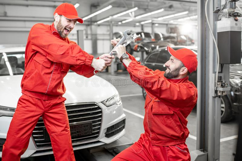Auto mechanics fighting with wrenches in the car service. Funny portrait of two auto mechanics in red uniform fighting with wrenches in the car service stock images
