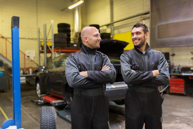 Auto mechanics or tire changers at car shop royalty free stock images