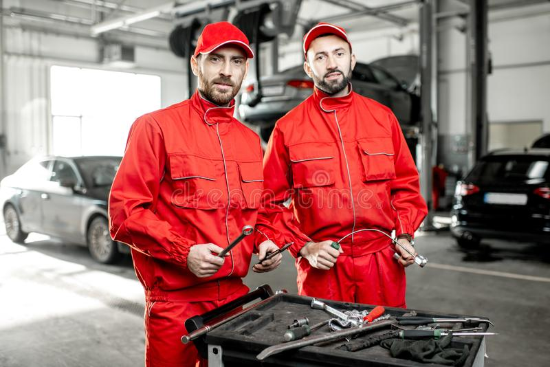 Auto mechanics with wrenches at the car service. Portrait of a two handsome auto mechanics in red uniform standing with working tools at the car service stock photos