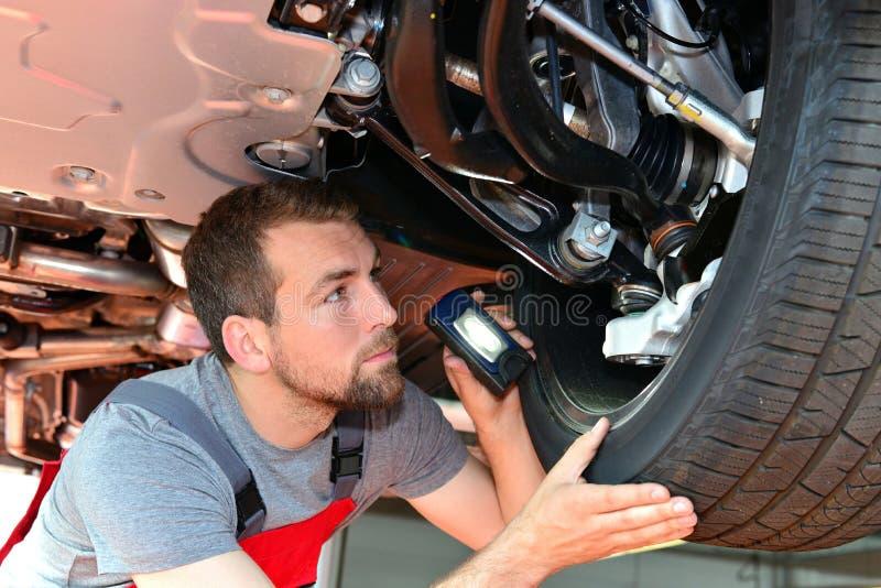 Auto mechanik naprawia pojazd w warsztacie zdjęcia stock