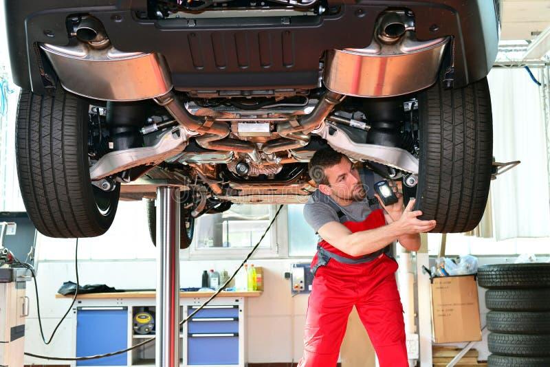 Auto mechanik naprawia pojazd w warsztacie zdjęcie stock